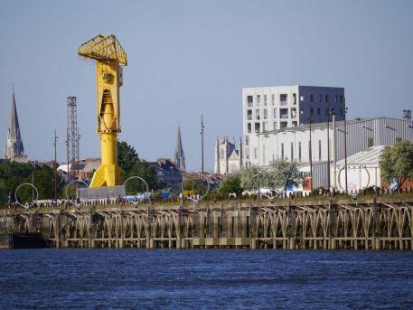 """Le quai des Antilles sur l'île de Nantes, """"les Anneaux"""" de Daniel Buren et Patrick Bouchain, la grue Titan jaune, vus depuis le bras de la Madeleine"""